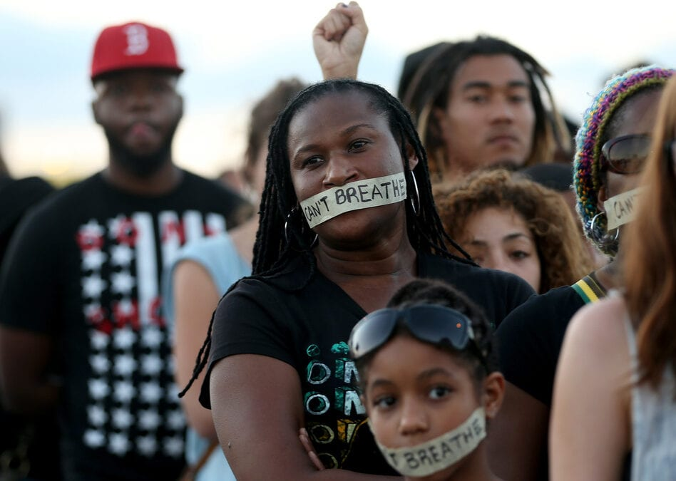 "Demonstrators in Miami stand with tape reading, "" I Can't Breathe,"" in 2014. The protest occurred after a grand jury in New York City declined to indict the police officers involved Eric Garner's death. © Getty Images"